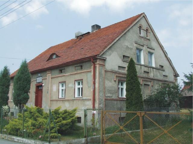 Według inskrypcji umieszczonej w elewacji frontowej zbudowany w roku 1864. Przez wiele lat zamieszkiwany był przez ks. Jana Dzierżonia, o czym informują tablice – niemiecka z 1925, a także późniejsza w języku polskim.  Usytuowany w centrum wsi, w p - MojRower.pl